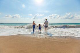 Na obrazku rodzina; kobieta, mężczyzna i dziewczynka. Rodzina spaceruje w kierunku spienionych fal morskich. W tle morskie fale