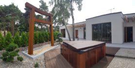 Na obrazu 2 wolnostojące apartamenty, przed nimi nakryte jacuzzi, panel z prysznicem oraz w otoczeniu drzewa i ogród.